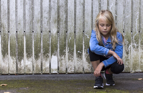 Portrait of serious blond girl crouching in front of wooden wall - JFEF00926