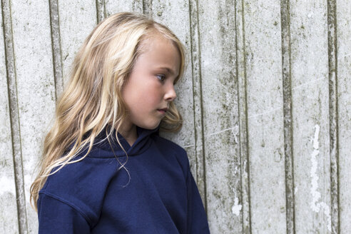 Profile of sad blond girl leaning against wooden wall - JFEF00935