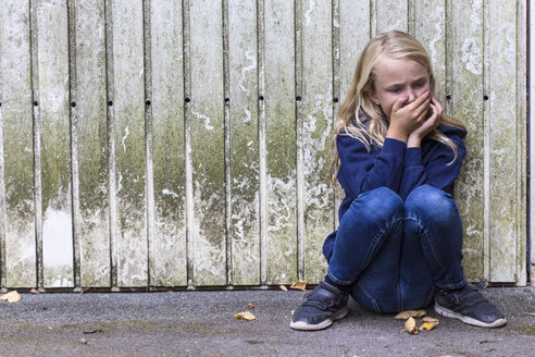 Frightened girl crouching in front of wooden wall - JFEF00938