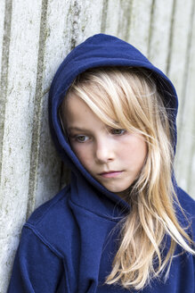 Portrait of sad blond girl wearing blue hooded jacket leaning against wooden wall - JFEF00941