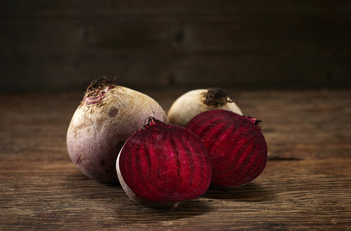 Whole and sliced beetroot on dark wood, copy space - KSWF02000