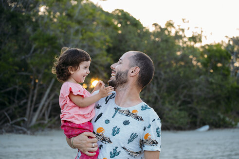 Australia, Queensland, Mackay, Cape Hillsborough National Park, happy father holding his daughter at the beach at sunset - GEMF02572