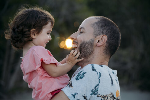Happy father holding his daughter outdoors at sunset - GEMF02575
