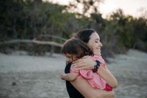 Australia, Queensland, Mackay, Cape Hillsborough National Park, happy mother hugging her daughter at the beach - GEMF02578