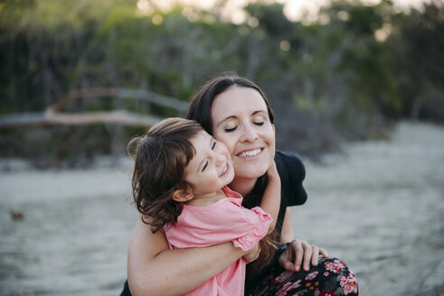 Australia, Queensland, Mackay, Cape Hillsborough National Park, happy mother hugging her daughter at the beach - GEMF02581