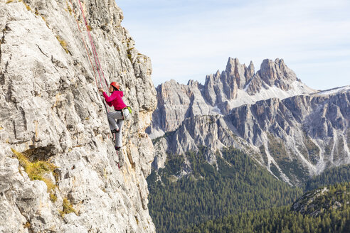 Italy, Cortina d'Ampezzo, woman climbing in the Dolomites mountains - WPEF01147