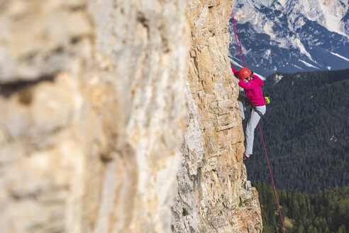 Italy, Cortina d'Ampezzo, woman climbing in the Dolomites mountains - WPEF01153