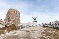 Italy, Cortina d'Ampezzo, happy hiker jumping at the top of the mountain in the Dolomites mountains - WPEF01159
