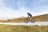 Italy, Cortina d'Ampezzo, panning view of man cycling with mountain bike in the Dolomites mountains - WPEF01162