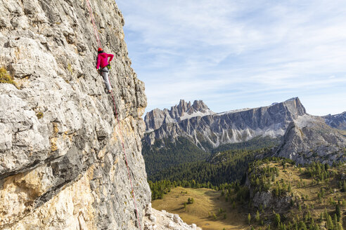 Italy, Cortina d'Ampezzo, woman using chalk poweder while climbing in the Dolomites mountains - WPEF01168