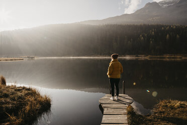 Switzerland, Engadine, Lake Staz, woman standing on a jetty at lakeside in morning sun - LHPF00142