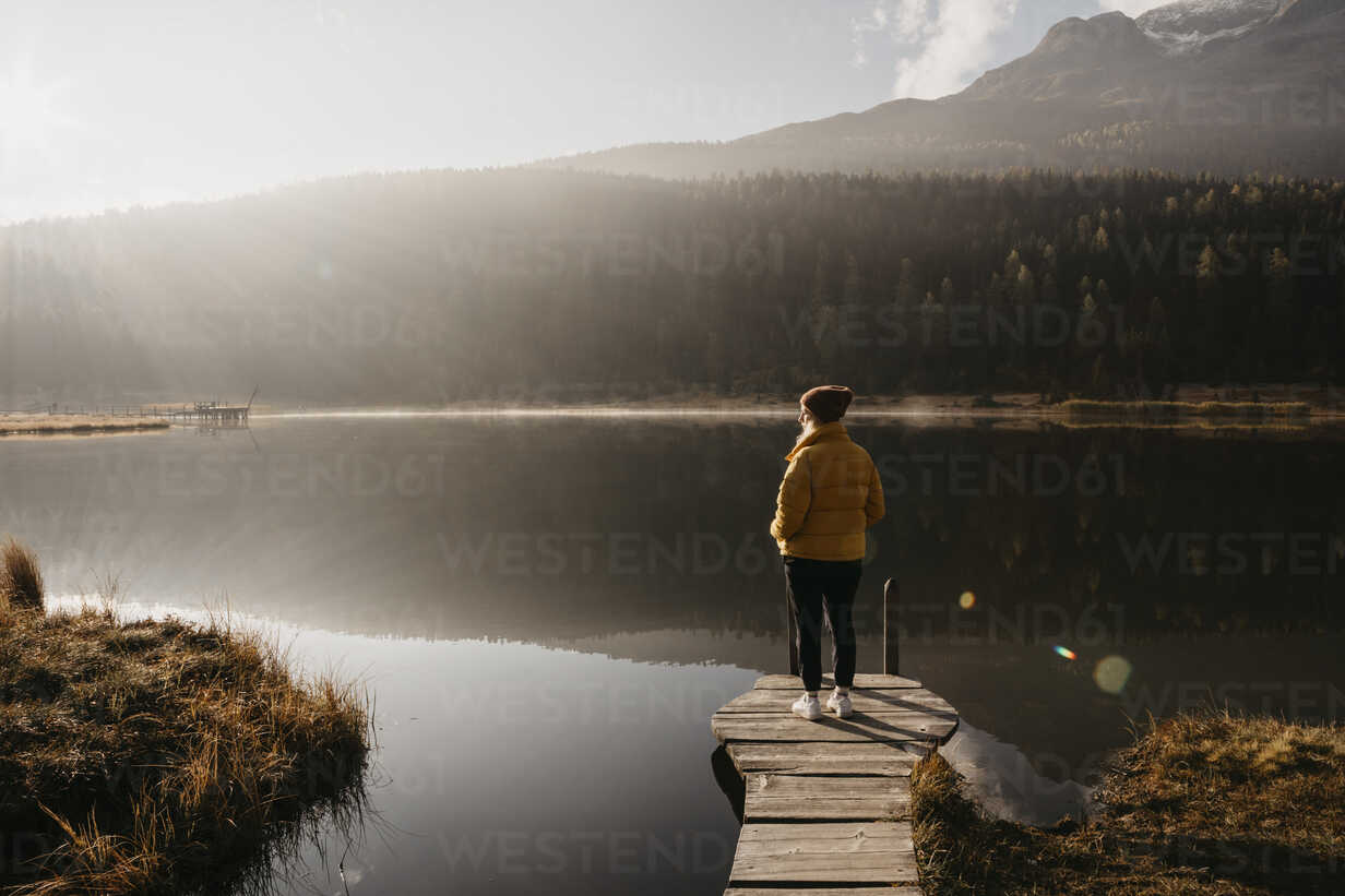 Switzerland, Engadine, Lake Staz, woman standing on a jetty at lakeside in morning sun - LHPF00142 - letizia haessig photography/Westend61