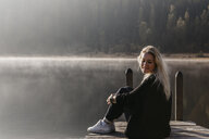 Switzerland, Engadine, Lake Staz, smiling young woman sitting on a jetty at lakeside in morning sun - LHPF00145