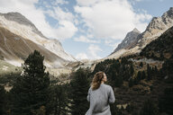 Switzerland, Grisons, Albula Pass, woman standing in mountainscape - LHPF00151