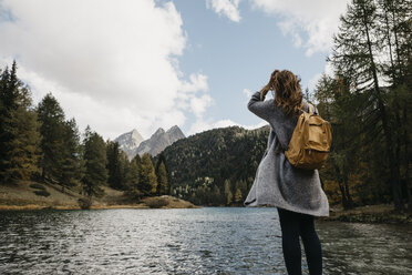 Switzerland, Grisons, Albula Pass, woman on a hiking trip standing at lakeside in mountainscape - LHPF00154