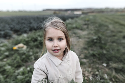 Portrait of a girl standing on a cabbage field - KMKF00673