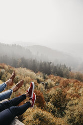 Germany, Black Forest, Sitzenkirch, legs of two women sitting at Sausenburg Castle above mountain forest - LHPF00162