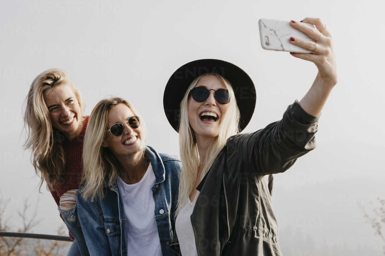 Three happy young women taking a selfie outdoors - LHPF00168 - letizia haessig photography/Westend61