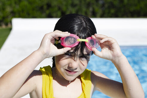 Portrait of little girl wearing swimming goggles at pool - ERRF00155
