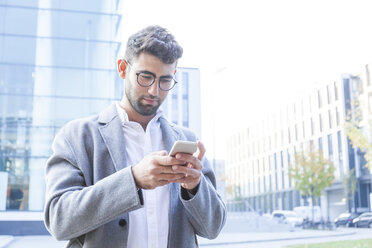Portrait of young businessman using cell phone - TCF05984