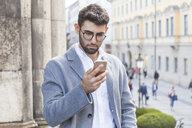 Germany, Munich, portrait of young businessman using cell phone in the city - TCF05987