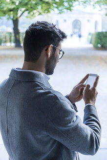 Germany, Munich, young businessman text messaging - TCF05990
