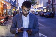 Germany, Munich, young businessman using digital tablet in the city at dusk - TCF05999