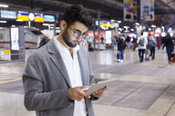 Germany, Munich, young businessman using digital tablet at central station - TCF06002