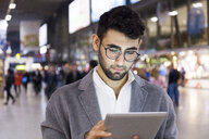 Germany, Munich, portrait of young businessman using digital tablet at central station - TCF06005