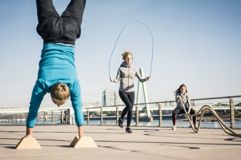 Friends training at the riverside, skipping rope and doing handstand - MOEF01667