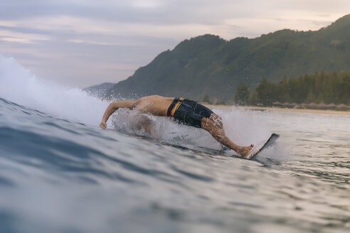Shirtless man surfing on sea against cloudy sky during sunset - CAVF56522