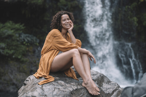 Portrait of smiling woman sitting on rock against waterfall in forest - CAVF56531