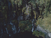 Mid distance view of woman in bikini enjoying waterfall at forest - CAVF56534
