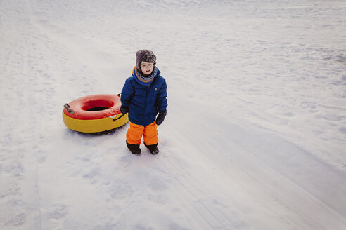 High angle view of boy holding tube sled while walking on snow covered field - CAVF56561