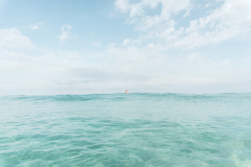 Mid distance view of man swimming in sea against sky - CAVF56573