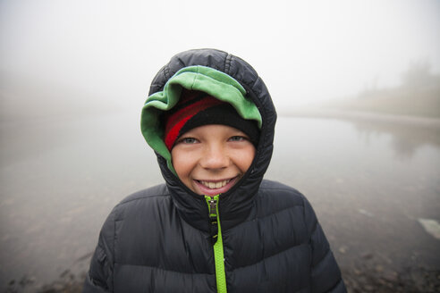 Portrait of smiling boy wearing warm clothing against lake during foggy weather - CAVF56606