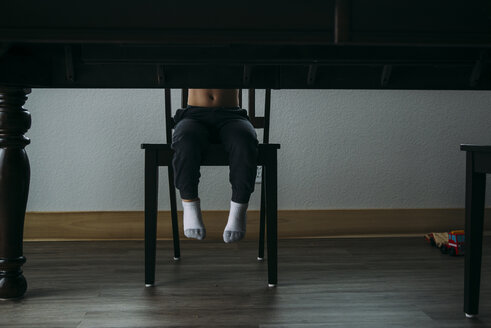 Low section of boy sitting on chair by table at home - CAVF56615