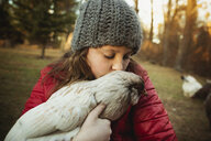 Girl kissing chicken while standing at poultry farm - CAVF56636