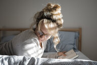 Side view of woman reading book while lying on bed at home - CAVF56648
