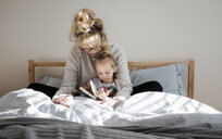 Mother with daughter reading book while sitting on bed at home - CAVF56651