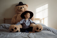 Boy with teddy bear sitting on bed at home - CAVF56654