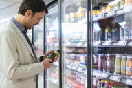 Mature man in supermarket choosing smoothie from cooling shelf - DIGF05489