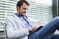 Businessman sitting on a bench, using digital tablet - DIGF05507