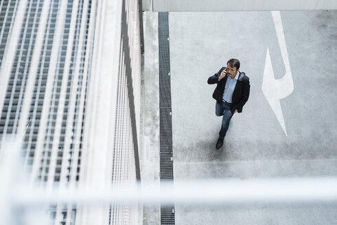Businessman walking in parking garage, using mobile phone - DIGF05522