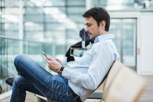 Businessman waiting in airport departure area, using digital tablet - DIGF05525