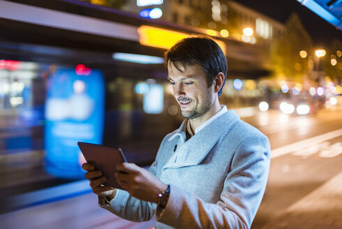 Businessman with digital tablet standing at a bus stop at night - DIGF05561