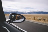 Reflection of woman photographing seen in side-view mirror against mountains and cloudy sky - CAVF56677