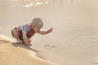 Baby boy playing with water while sitting at beach - CAVF56689