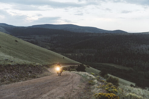 Biker riding motorbike on dirt road against sky in forest during sunset - CAVF56695