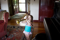 High angle view of girl playing trumpet while standing by piano at home - CAVF56701